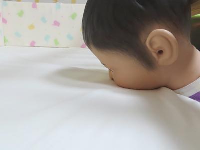 ベッド内でうつ伏せの状態になっている乳児ダミー人形頭部の写真。頭部は隙間に挟まり口と鼻が敷具に押し付けられている。